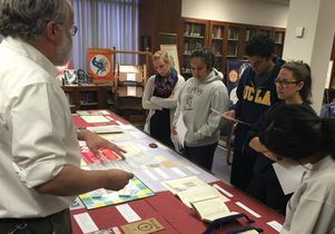 Students in a Fiat Lux class look at historicartifacts that promoted smoking and campaigned against it