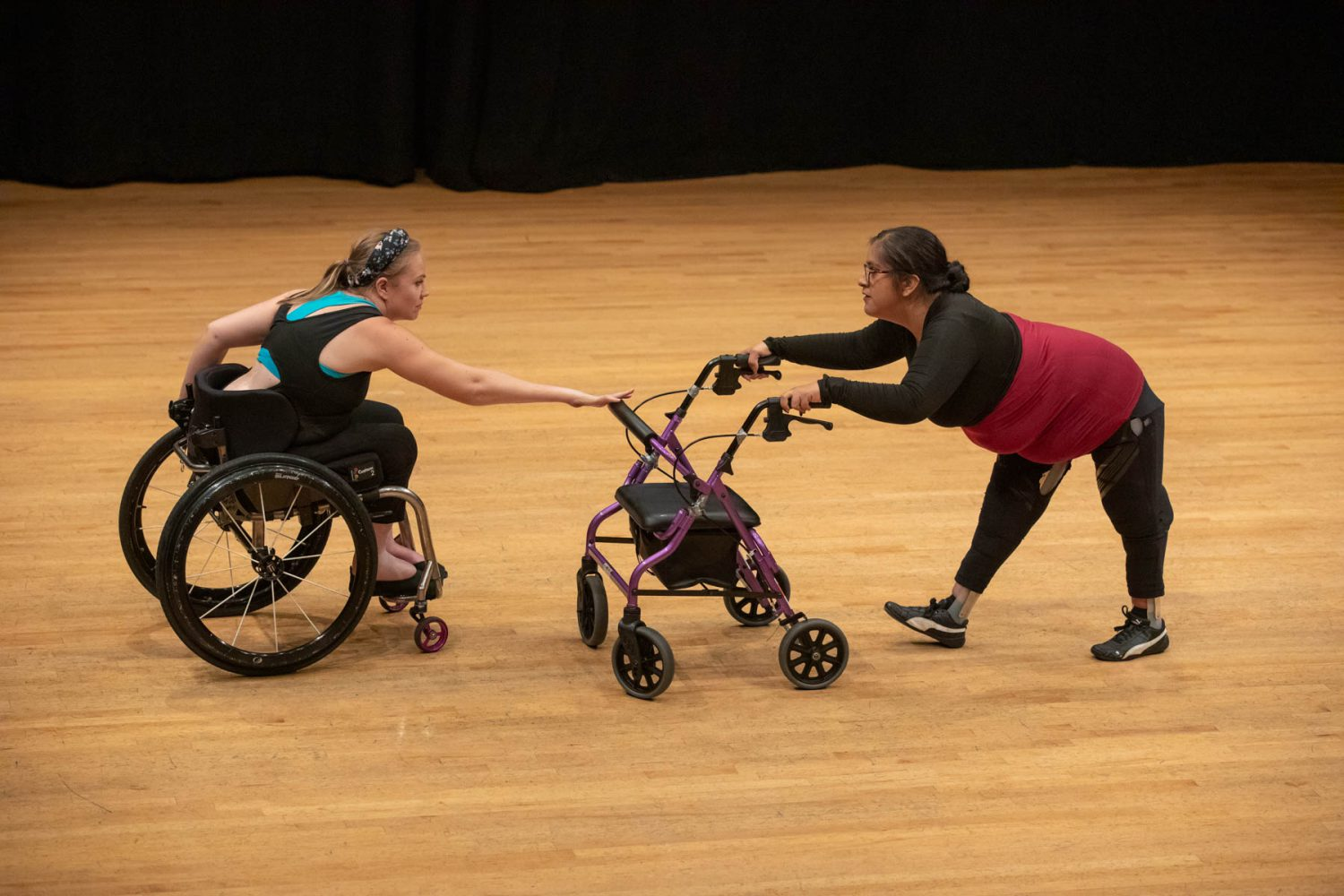 Harmonie in her wheelchair with her back lowered and right arm extended out touching Pluto. Vanessa opposite of Pluto and Harmonie with her back lowered and hands holding Pluto's handles as she watches Harmonie.