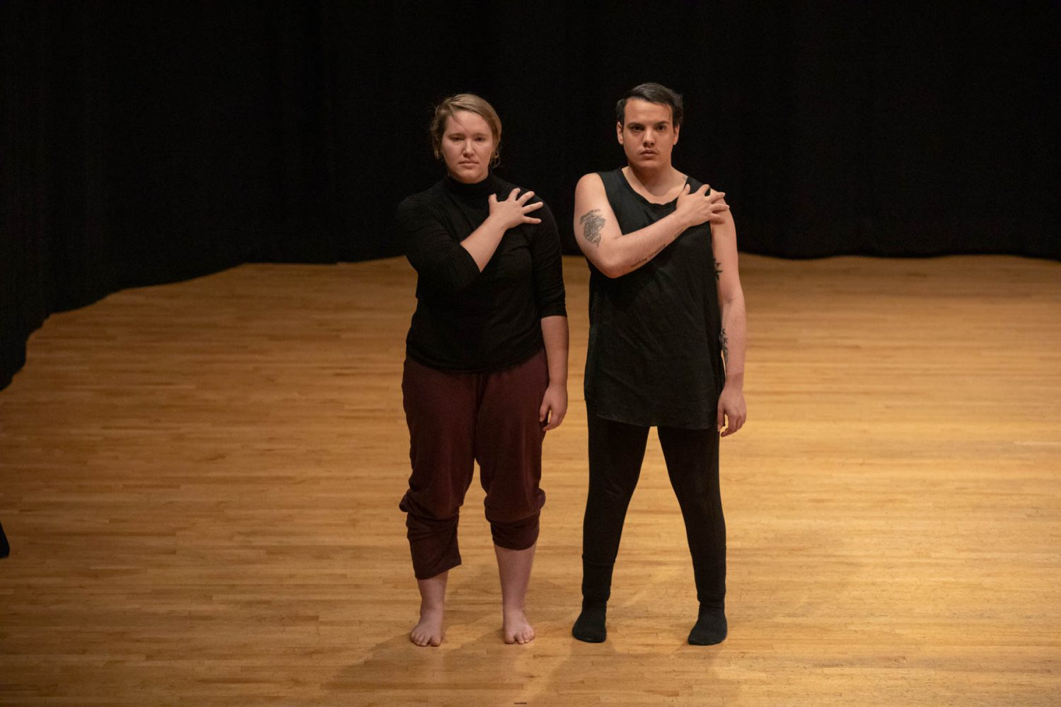 ) Bailey and Mark standing side by side. Both dancers have their right hands, fingers splayed, on their left shoulders.