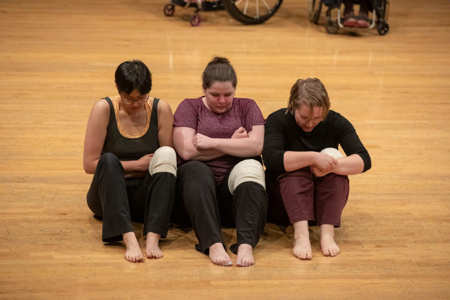 Mel, Margaret, and Bailey seated closely in a row on the floor with their knees and arms close to their bodies.