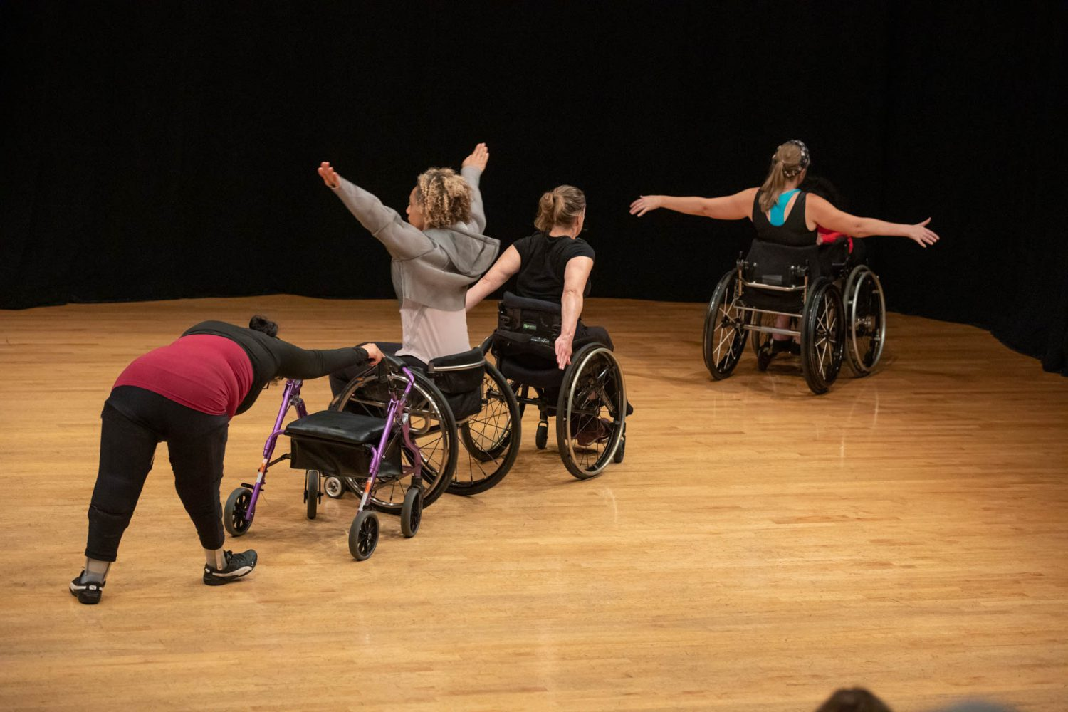 Five dancers, each in a different pose, line up in a diagonal row with their backs to the audience.