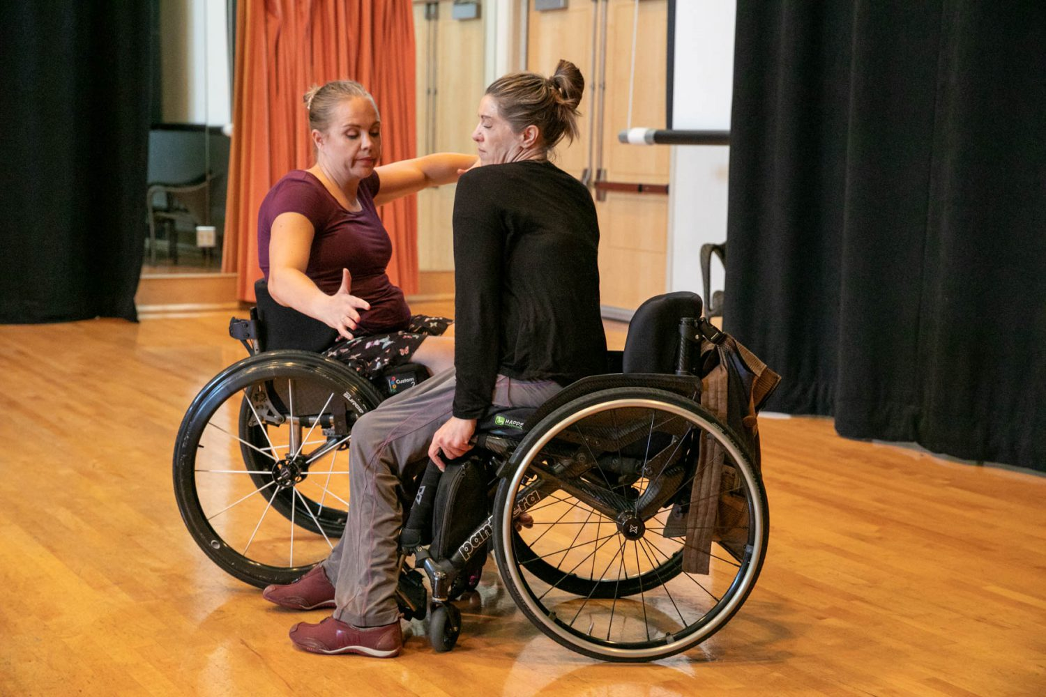 Harmonie and Suzanne, both in wheelchairs, dance closely together.