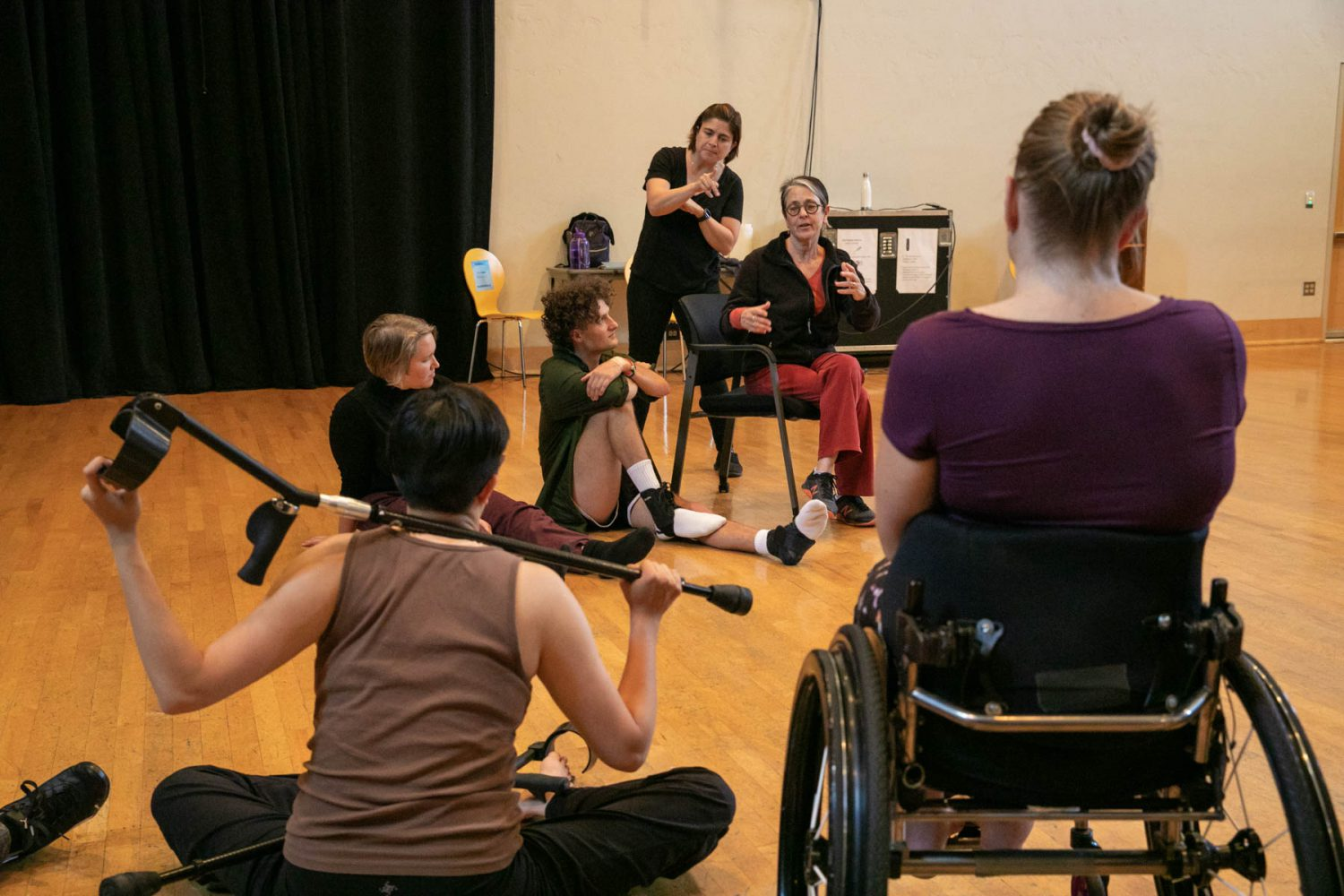 Four dancers in a studio looking to Victoria Marks as she speaks. An ASL interpreter is behind Victoria.